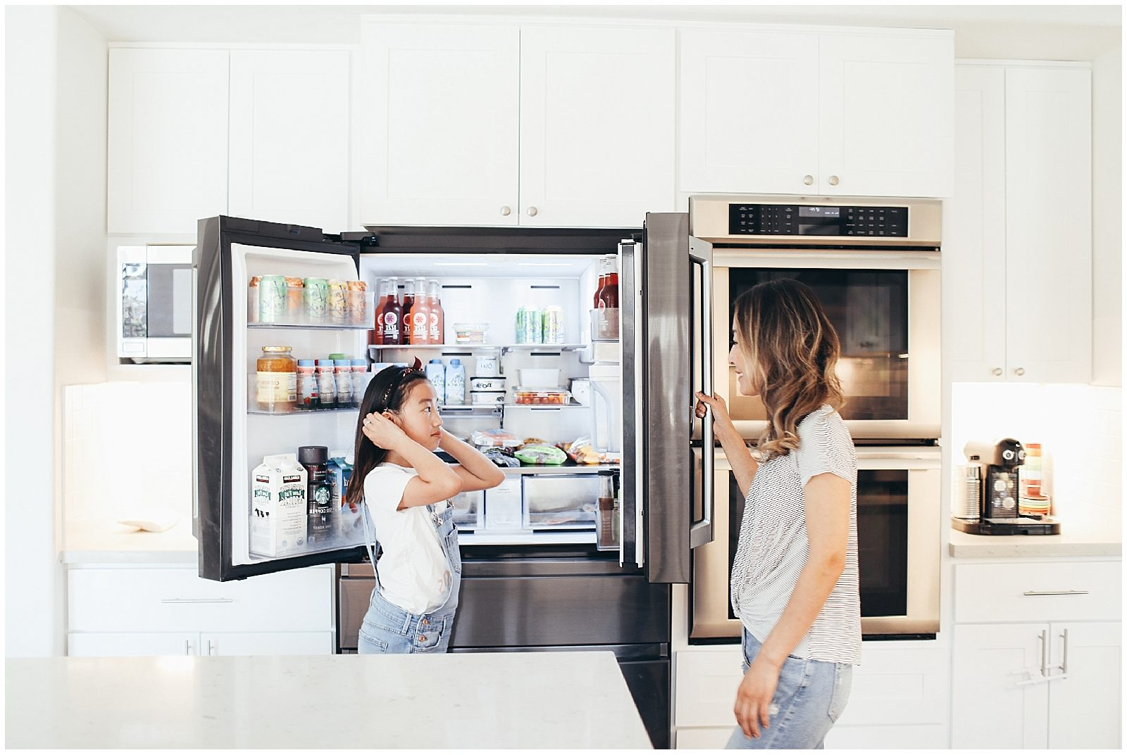 Mom and her daughter talking in the kitchen while they close the french door refrigerator.