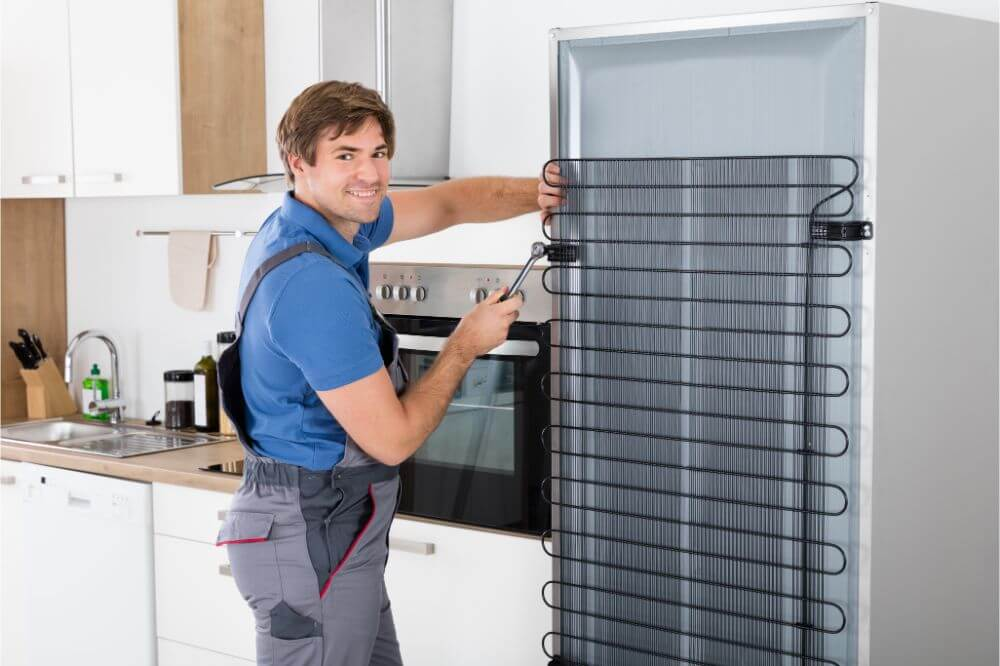 Repairman fixing refrigerator