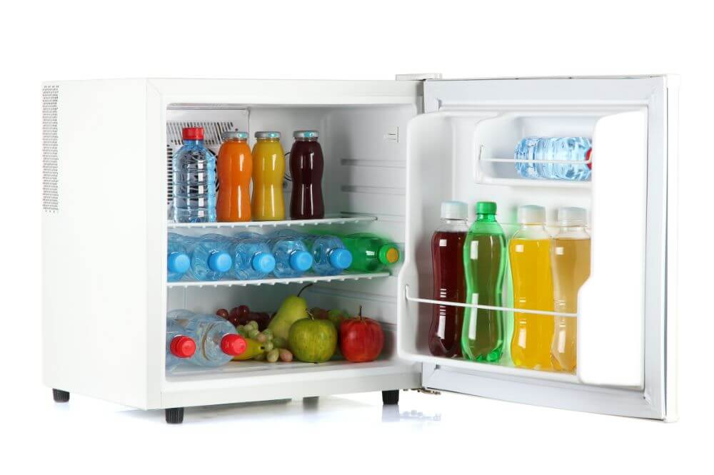 Mini fridge with lots of fruits, bottled juice and water