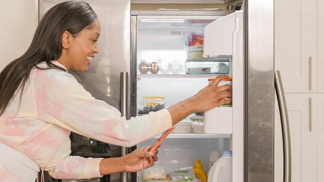 girl opening fridge